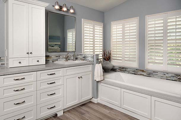 White cabinetry, bath and large mirror - large image
