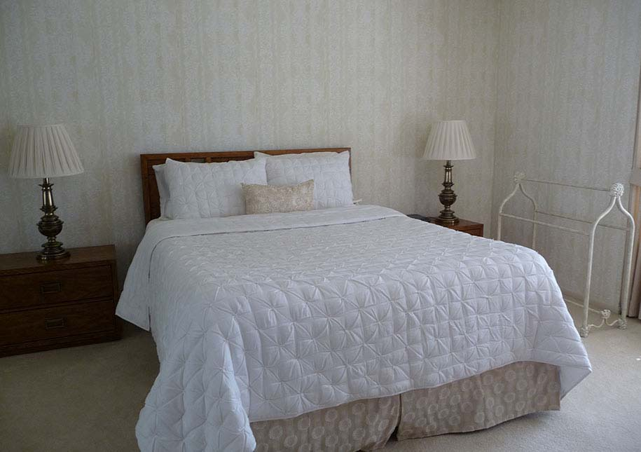 BEFORE: bedroom with wallpaper, old lamps, dark night stands - x-large photo